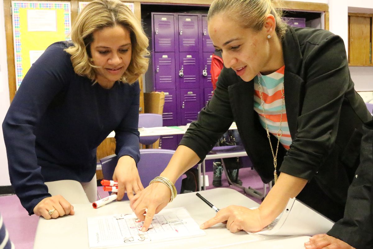 West Prep Academy teacher Annery Quezada (left) plays a math-themed game with parent Yenny Carrasco (right) at a recent APTT meeting.