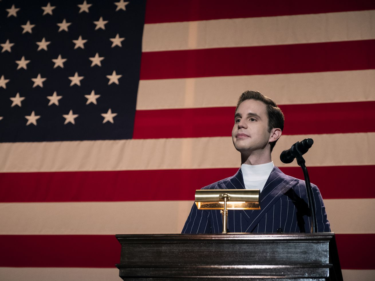 "Ben Platt as ""The Politician"" stands behind a podium in front of a wall covered with an American flag."