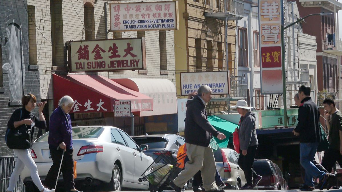 People walking across a street in Chinatown. Shop signs in Chinese can be seen above.