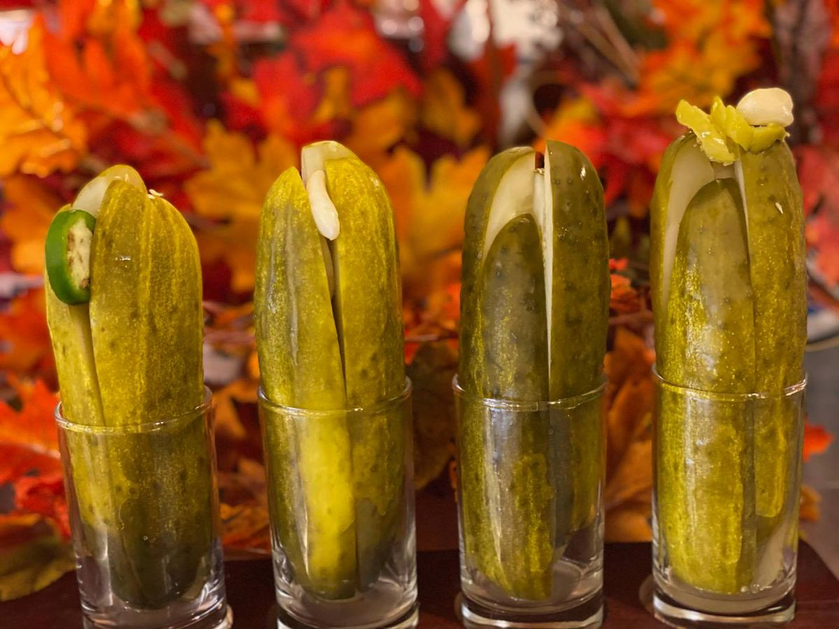 Four small glasses filled with spears of pickles against an orange floral backdrop