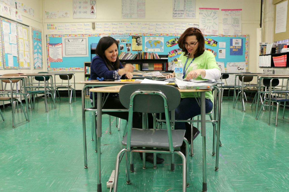 Fiorella Guevara, left, looked at student writing samples with a bilingual teacher at M.S. 50 in Williamsburg.