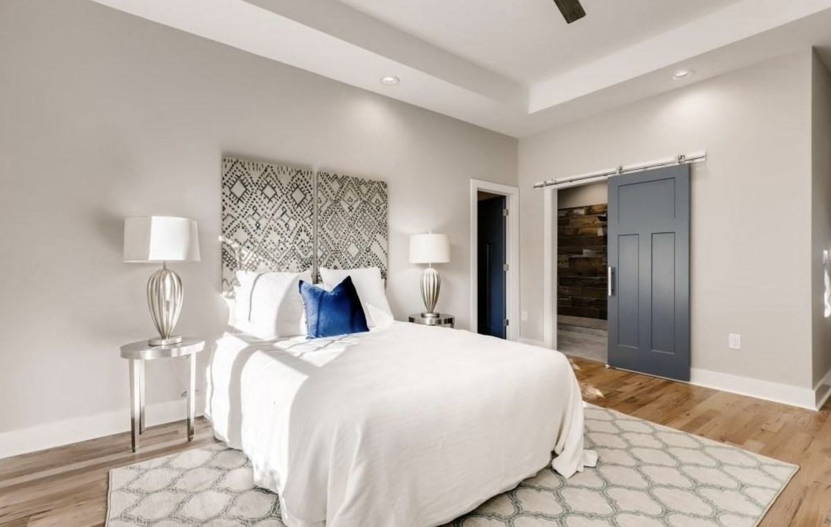 Bedroom with bed, nightstands with lamps, area rug, wall art behind the bed, and a gray barn door on the closet.
