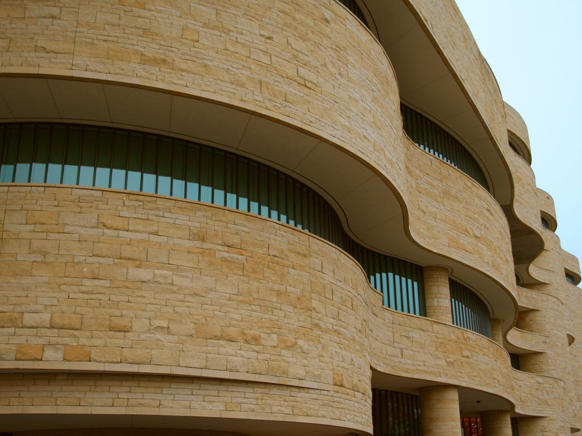 The exterior of a museum building. The exterior is undulating and has horizontal rows of windows.