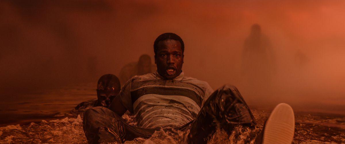 Dehşete kapılmış bir Siyah adam, arka planda beliren gölgeli figürlerle sisli turuncu bir manzarada oturuyor.