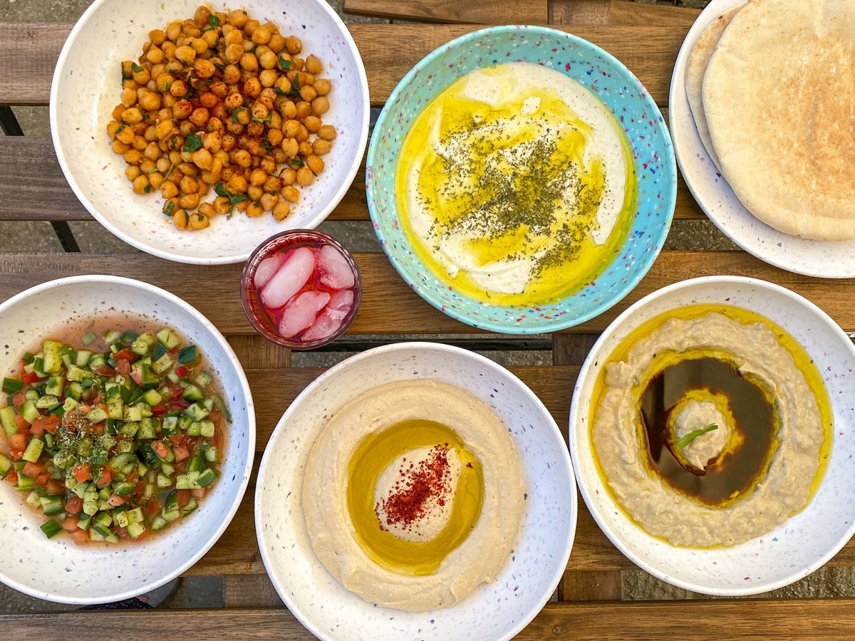 A photo of a spread of hummus, Persian cucumber salad, muttabal eggplant dip, vegan soy labneh, and chickpea salad from Alley Mezza