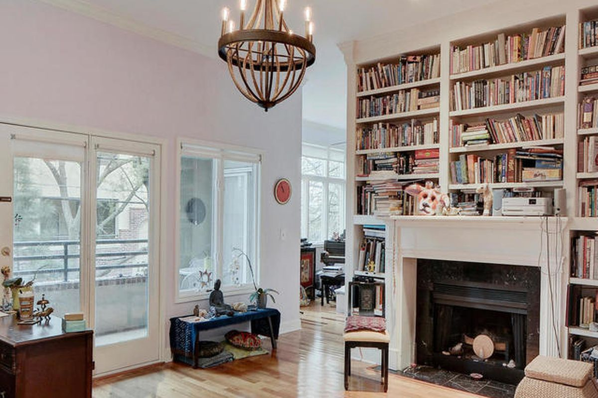 white-walled condo living room with tall ceilings, full built-in bookshelves, fireplace, large windows and glass door, balcony