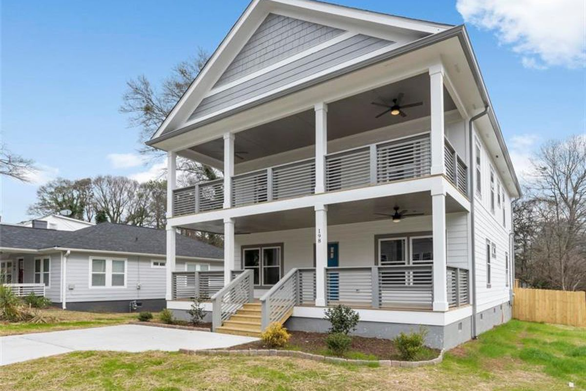 A two-story home for sale that's white and gray with two porches.