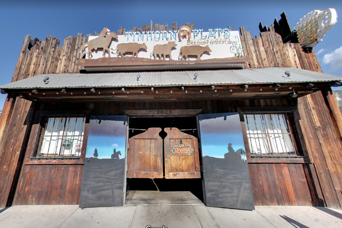A Western-themed bar from the front, at an angle, showing saloon doors and blue skies beyond.