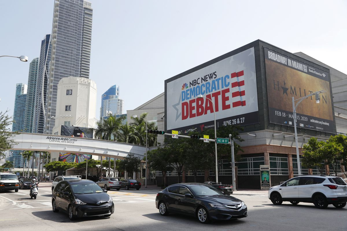 Cars pass by a billboard advertising the Democratic presidential debates across from the Knight Concert Hall at the Adrienne Arsht Center for the Performing Arts of Miami-Dade County, Tuesday, June 25, 2019, in Miami. The debates were held June 26 and 27,