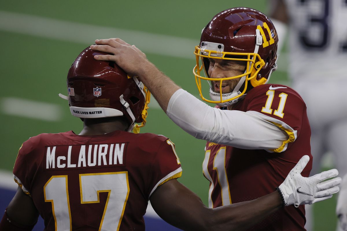 Alex Smith of the Washington Football Team celebrates with Terry McLaurin during the second quarter of a game against the Dallas Cowboys at AT&T Stadium on November 26, 2020 in Arlington, Texas.