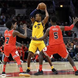 Utah Jazz guard Rodney Hood, center, looks to pass as Chicago Bulls guard Justin Holiday, left, and forward Bobby Portis guard during the second half of an NBA basketball game Wednesday, Dec. 13, 2017, in Chicago. The Bulls won 103-100. (AP Photo/Nam Y. Huh)