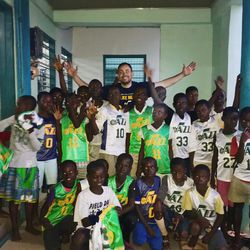 A group of Ghanaian children wear donated Jr. Jazz jerseys at a learning center in Abomosu. The center was built previously by World Joy of Bountiful, Utah. A group of Utah humanitarians from MRIoA and World Joy did fun crafts with the kids, making clothespin airplanes and popsicle stick picture frames. Zach Harding is in the background.