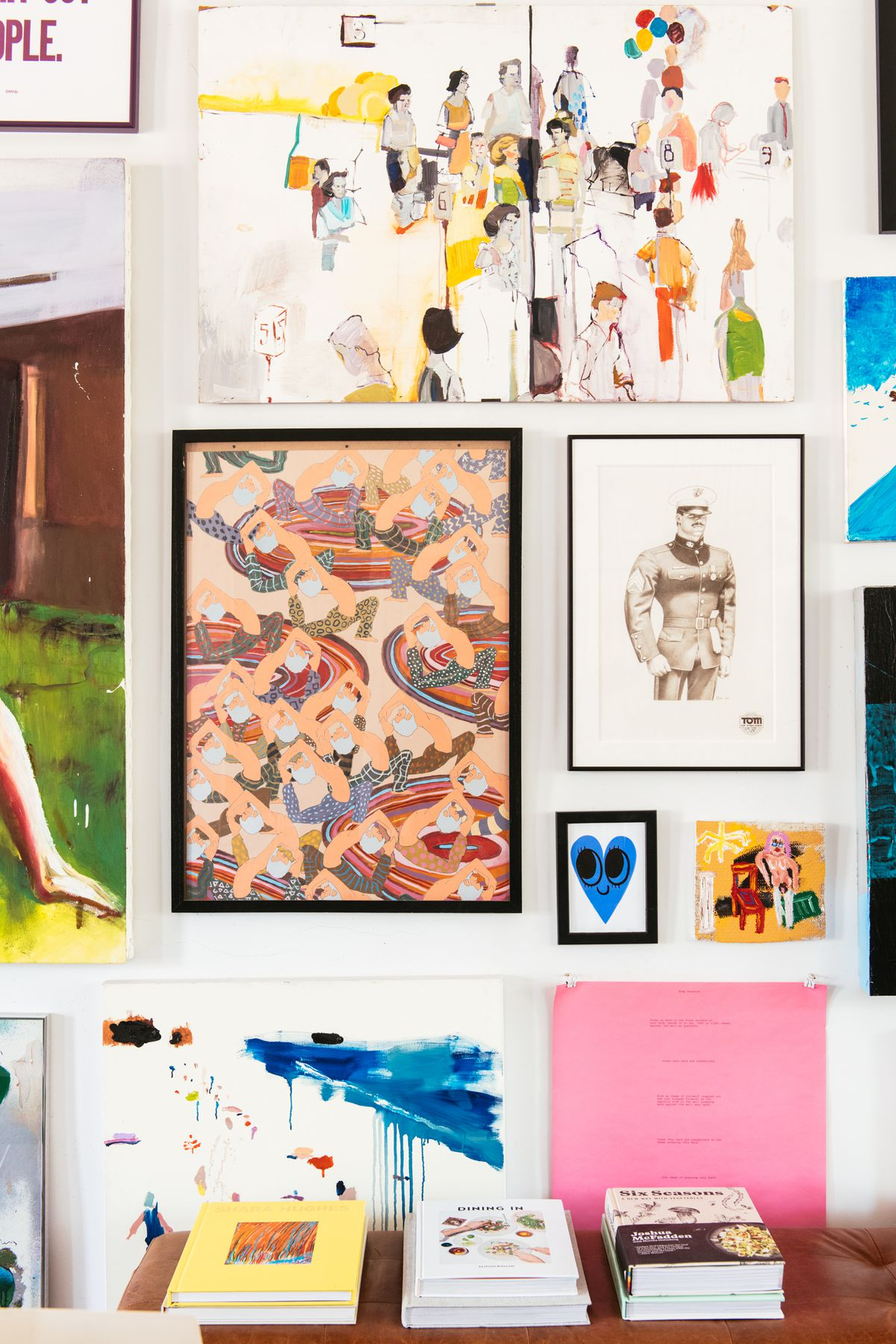 A painted white wall with multiple works of art hanging on the wall.