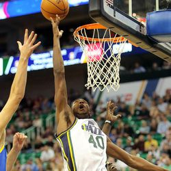 Utah's Jeremy Evans tips the ball up at the rim as the Utah Jazz and the Golden State Warriors play Tuesday, Oct. 8, 2013 in preseason action at Energy Solutions arena in Salt Lake City.