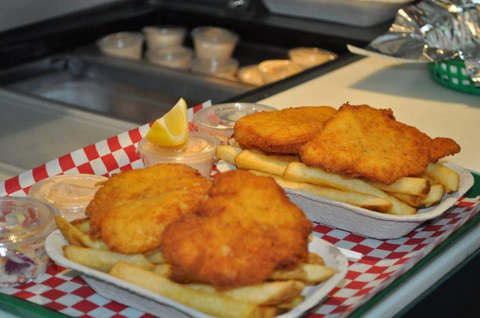 A view of fried fish with fries in containers on top of trays covered in red checkered paper.