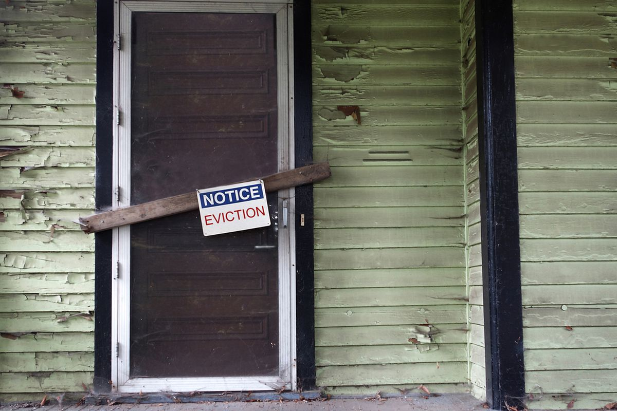 An eviction notice nailed to a boarded-up door.