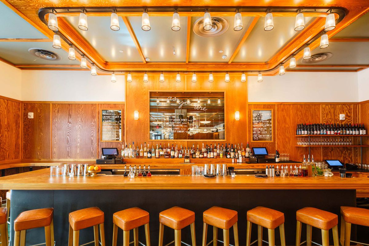 A bar with barstools, wood bar top, large mirror and Edison light bulbs.
