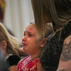 Alizea Gobel, 5, cries while watching a video of Matt Hall, her sister's father, during Hall's funeral at Myers Mortuary in Ogden on Saturday, April 15, 2017. Matt Hall was in jail for 15 months until he smashed his head into a wall and jumped off a railing in February. He was paralyzed from the shoulders down until dying from his injuries on April 7.