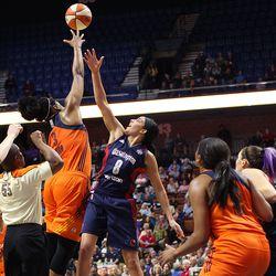 Connecticut Sun's Kelsey Bone (3) wins a jump ball over Washington Mystics' Bria Hartley (8) as Morgan Tuck and Stefanie Dolson battle for position.