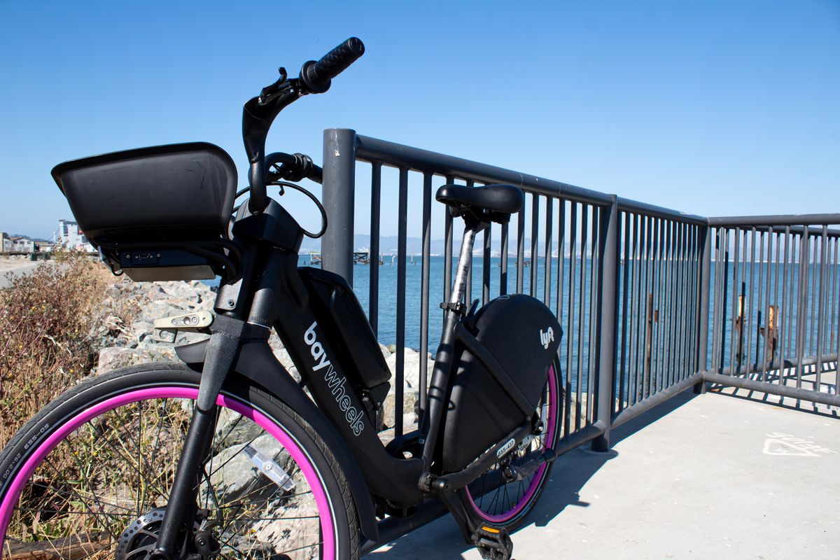 A black bike with pink rims sitting next to a fence with bay waters in the background.