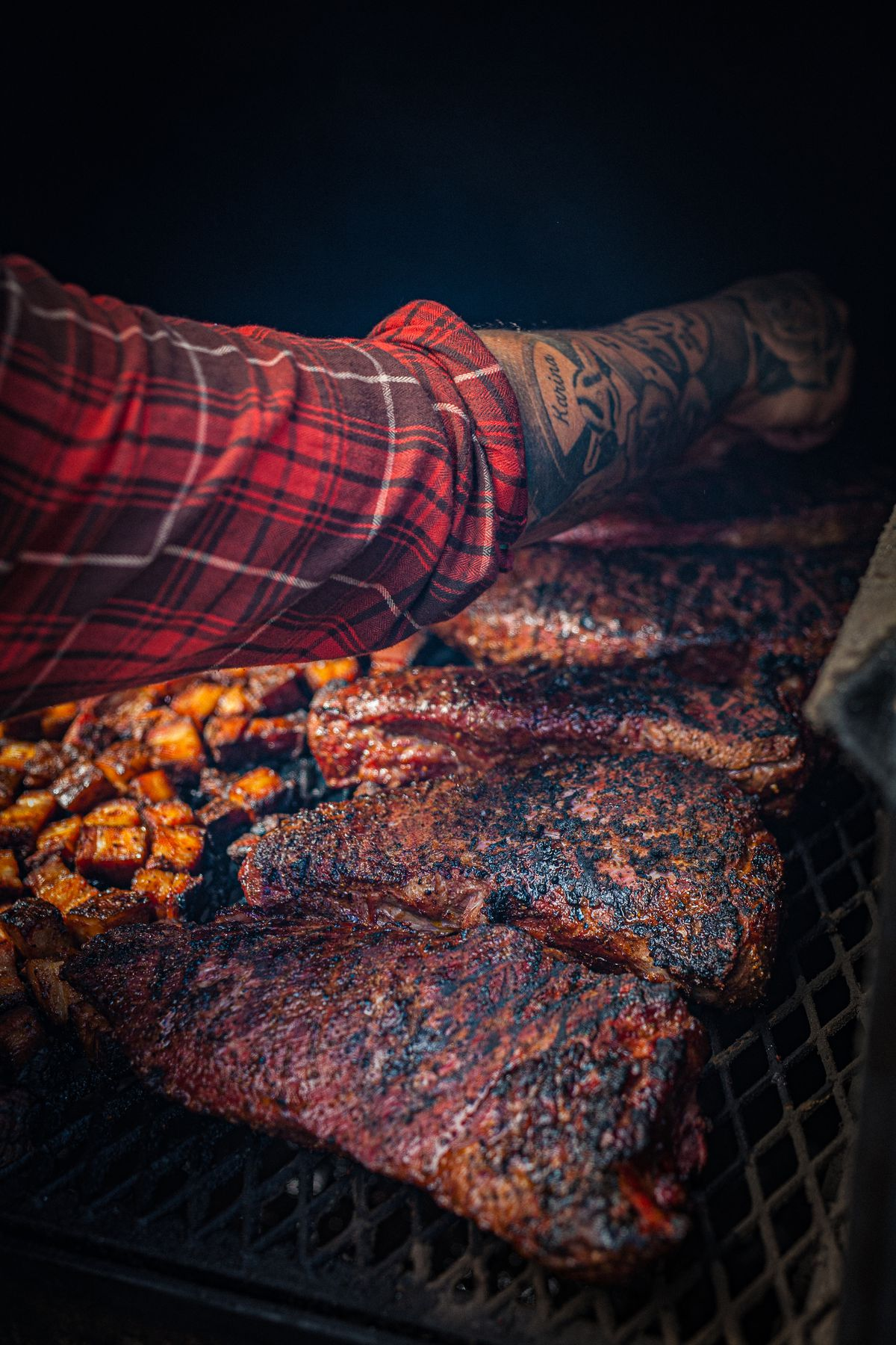 A red flannel arm works a big tray of ribs inside of a giant smoker.