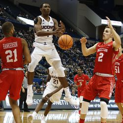 UConn's Christian Vital (1) loses control of the ball between two Boston University defenders.