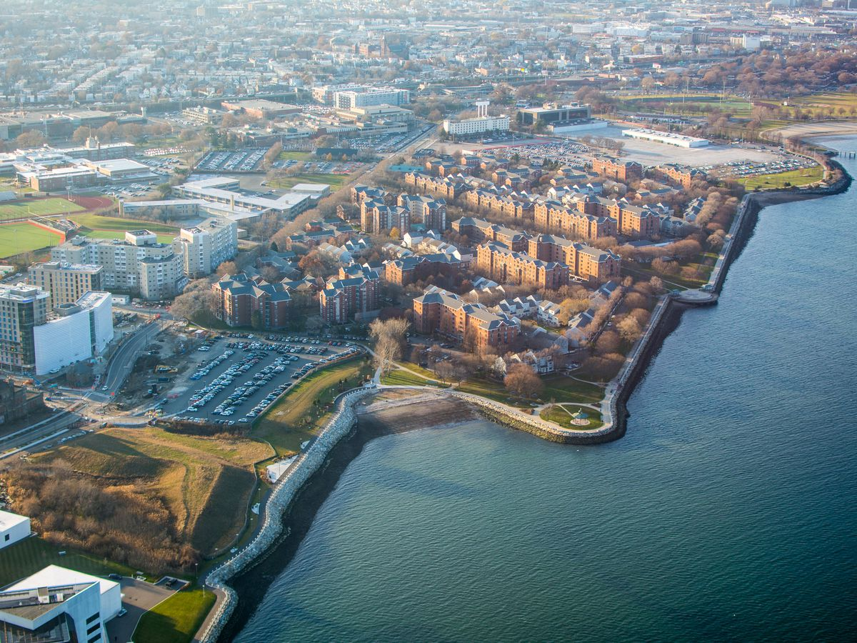 An aerial view of several buildings next to a waterfront.