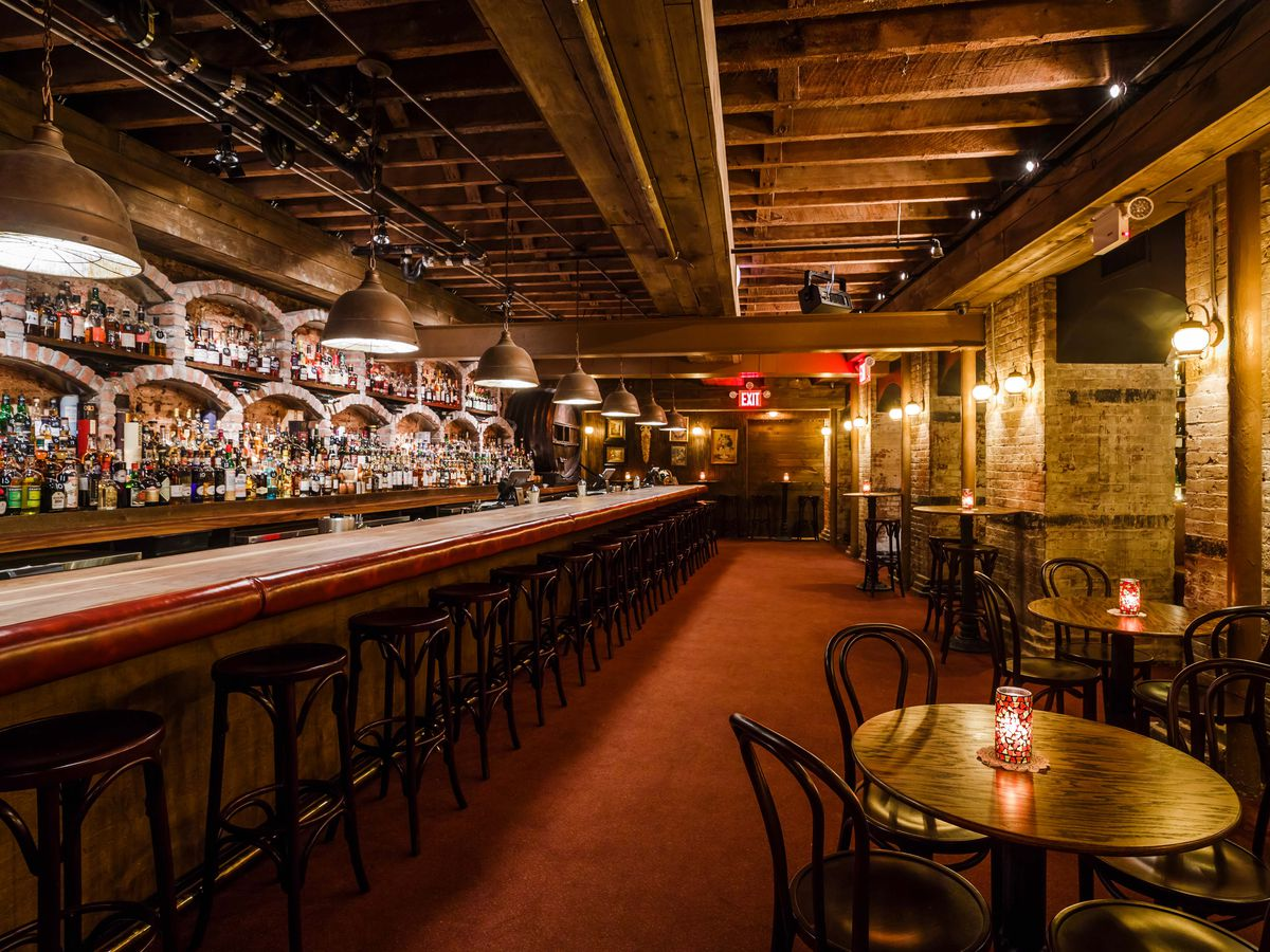 A long bar with low, small wood tables adjacent