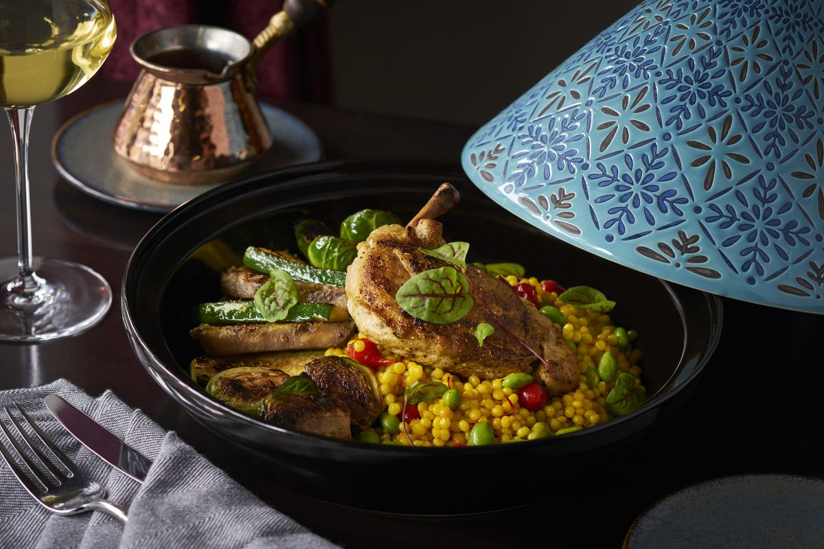 Chicken tajinewith Moroccan spices, saffron pearl couscous, and a harissa tomato sauce is served in a traditional vessel