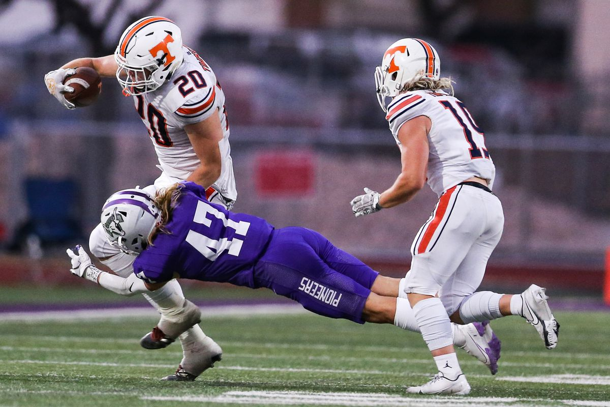 Timpview's Carsen Ryan (20) carries the ball against the Lehi defense during a high school football game at Lehi High School in Lehi on Friday, Sept. 25, 2020.