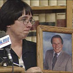Loydene Berg holds up a photo of her slain husband, Peter Berg, at a press conference in July 2002, after Quinn Martinez was sentenced.