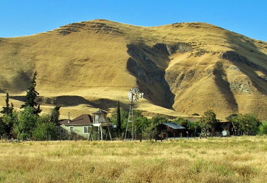 The exterior of Black Diamond Mines in California. There are multiple houses in front of a large hill. In the foreground is grass.