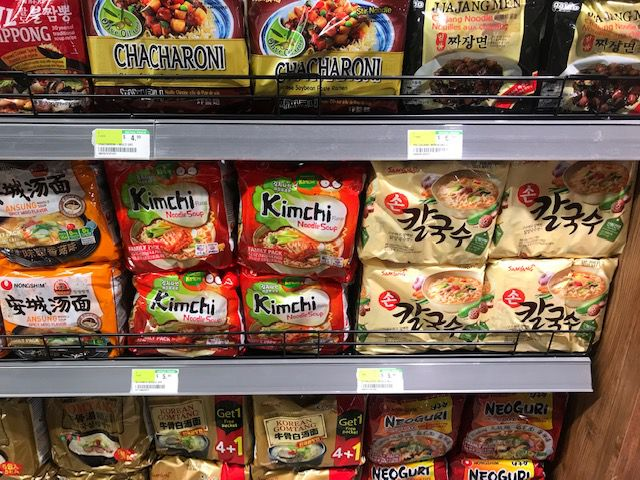 Shelves at District H, filled with kimchi packets and other Korean goods.