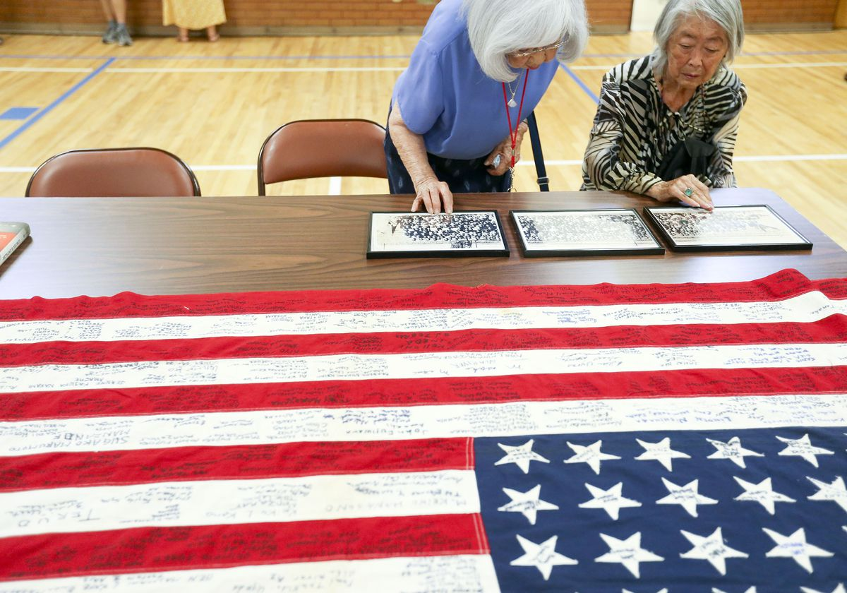 Jeanette Mitari Misaka, left, and Yoshiko Mayeda Uno look at photographs from World War II concentration camps such as Heart Mountain and Topaz at the Salt Lake Buddhist Temple on Wednesday.