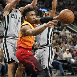 Utah Jazz's Donovan Mitchell, center, passes the ball as he is defended by San Antonio Spurs' Manu Ginobili (20) and Patty Mills during the second half of an NBA basketball game Friday, March 23, 2018, in San Antonio. San Antonio won 124-120 in overtime. (AP Photo/Darren Abate)