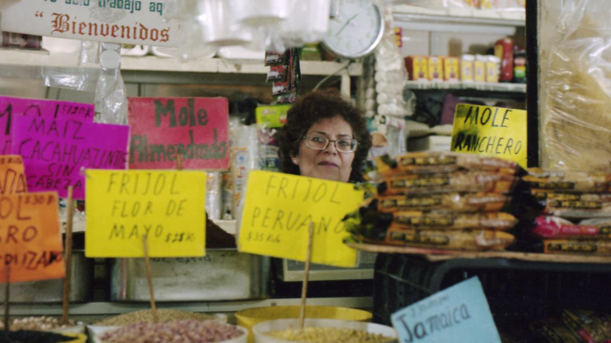 Jose Maria Teresa Martinez stands behind her stall of dry goods, displayed in buckets, with multicolored, handwritten signs in the foreground.