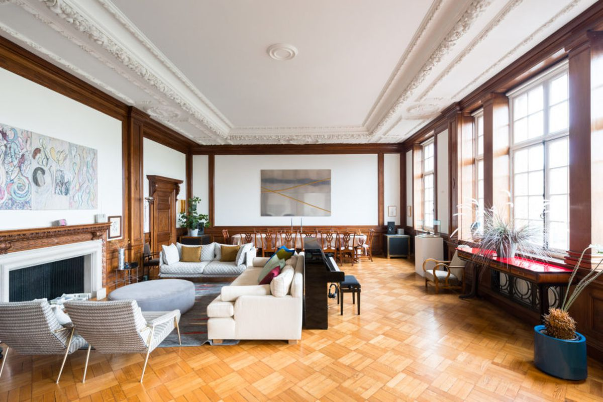 Interior of grand hall with white plaster crown molding, dark wood paneling, large windows on one wall, and parquet flooring, divided into living and dining zones.