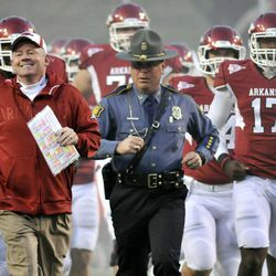 FILE - In this Nov. 12, 2011, file photo, Arkansas coach Bobby Petrino, left, followed by Arkansas State Police Captain Lance King, center, Brandon Mitchell (17) and  and the rest of the team onto the field before the start of an NCAA college football game against Tennessee in Fayetteville, Ark. The Bobby Petrino saga has left unsavory trails of deceit, including a troubling perception about the relationship between coaches and the police who handle security for them around the Southeastern Conference _ a region where college football reigns supreme. When Petrino wrecked his motorcycle in the hills outside of Fayetteville on April 1, the person he trusted most to handle the immediate aftermath was King, who provided security for the team at Razorback games.