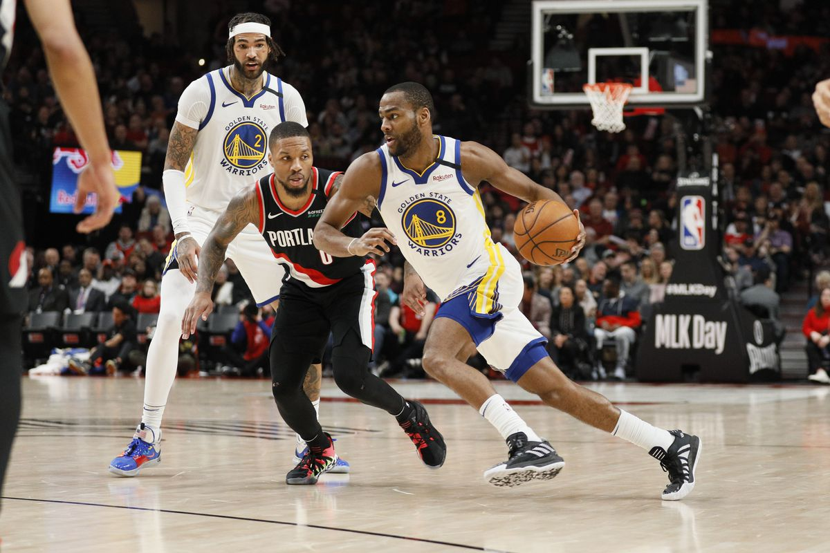 Golden State Warriors guard Alec Burks dribbles the ball as Portland Trail Blazers guard Damian Lillard defends during the second half at Moda Center.