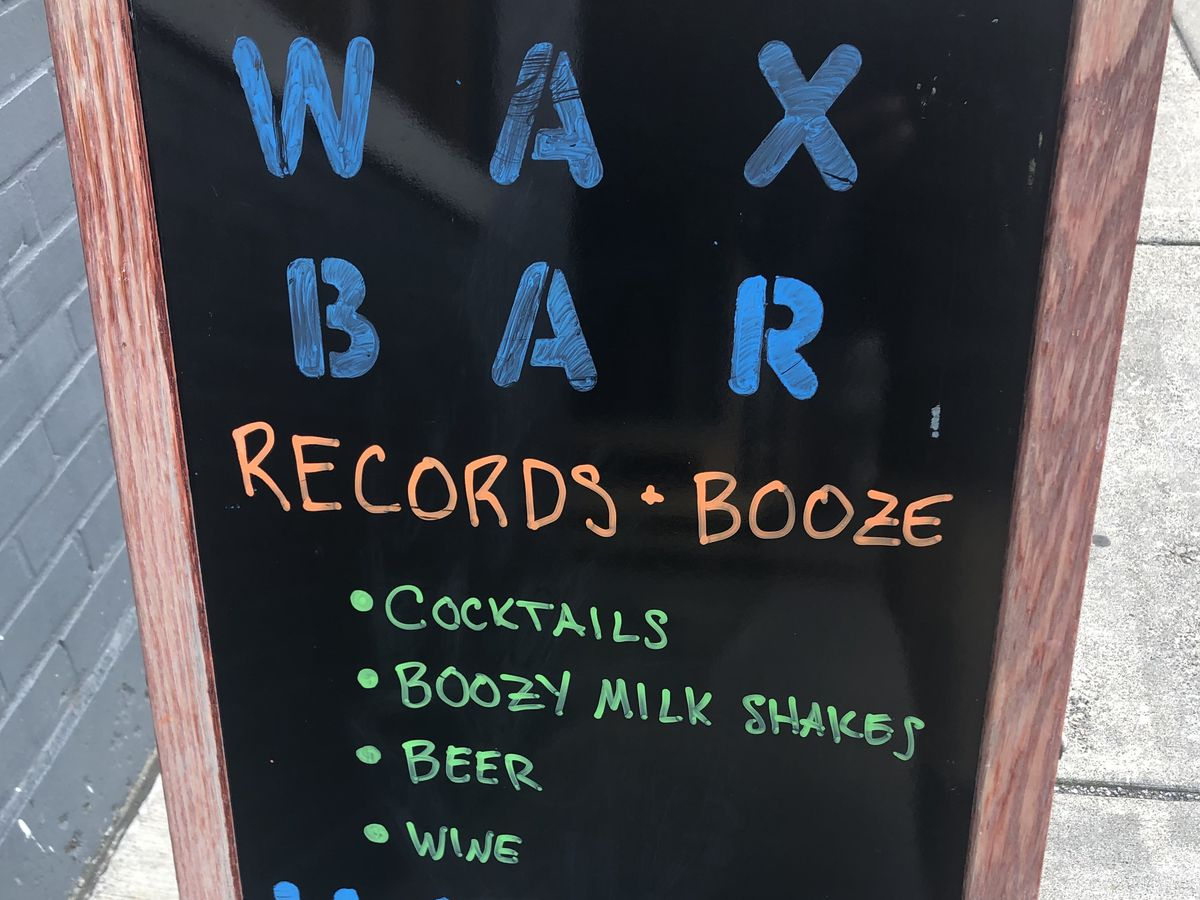 A sandwich board with Wax Bar written in neon letters. A list of services and happy hour times are written on the board.