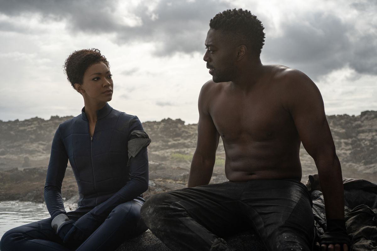 Sonequa Martin-Green sits next to shirtless David Ajala in a barren landscape on the water in Star Trek: Discovery
