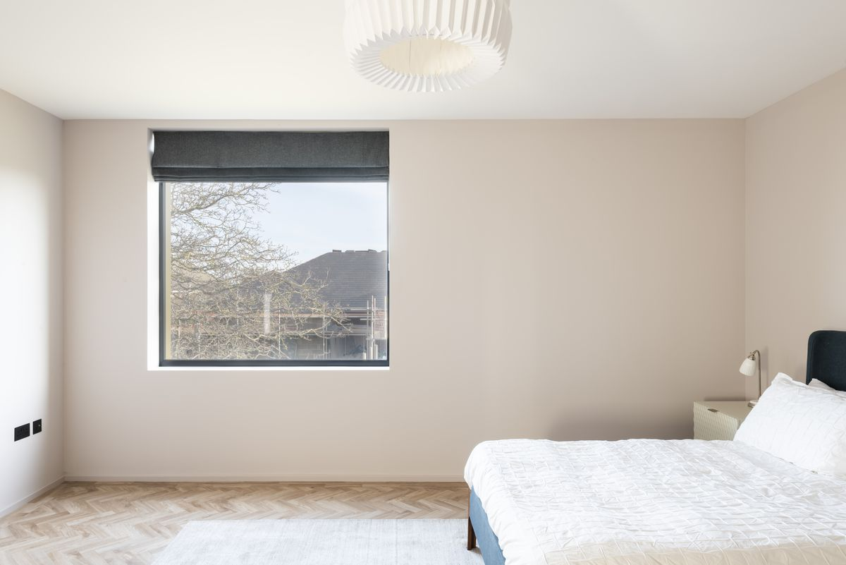 A bedroom with a large square window.