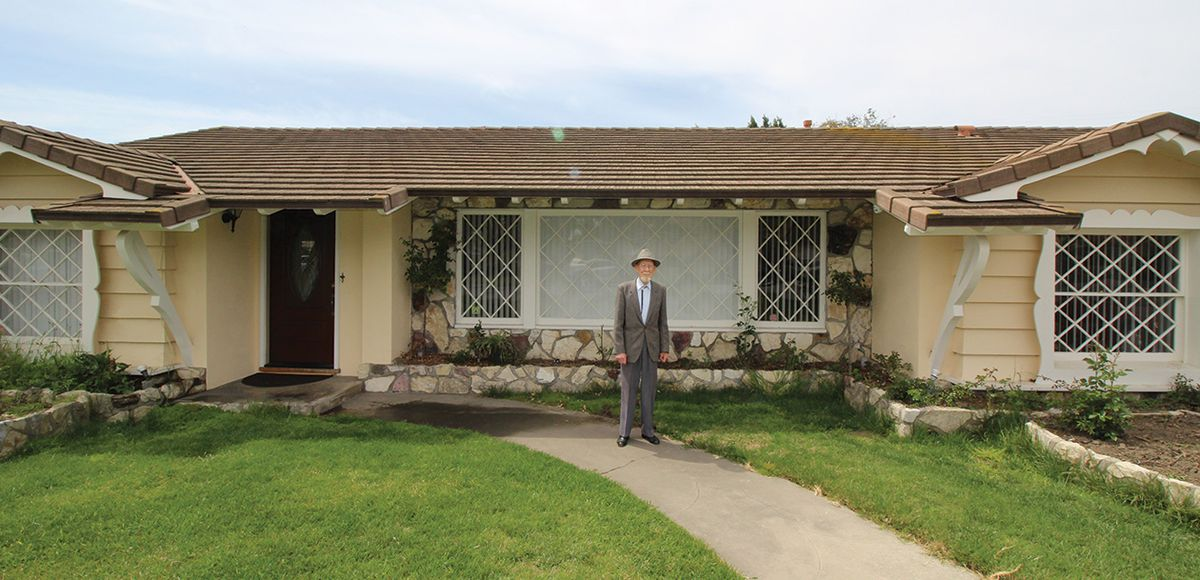 A man in a gray suit stands in front of a yellow house