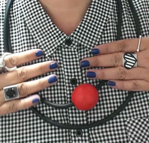 Woman wearing a black and white gingham shirt and a necklace consisting of two cords and a red ball.