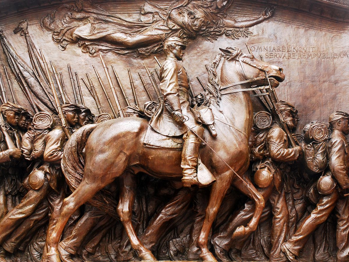 A bronze relief of an officer on horseback and his soldiers around him.