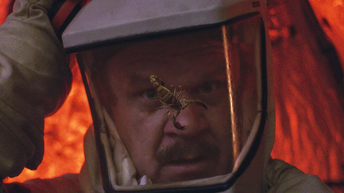 John C. Reilly in an astronaut suit faces a scorpion close-up in Moonbase 8