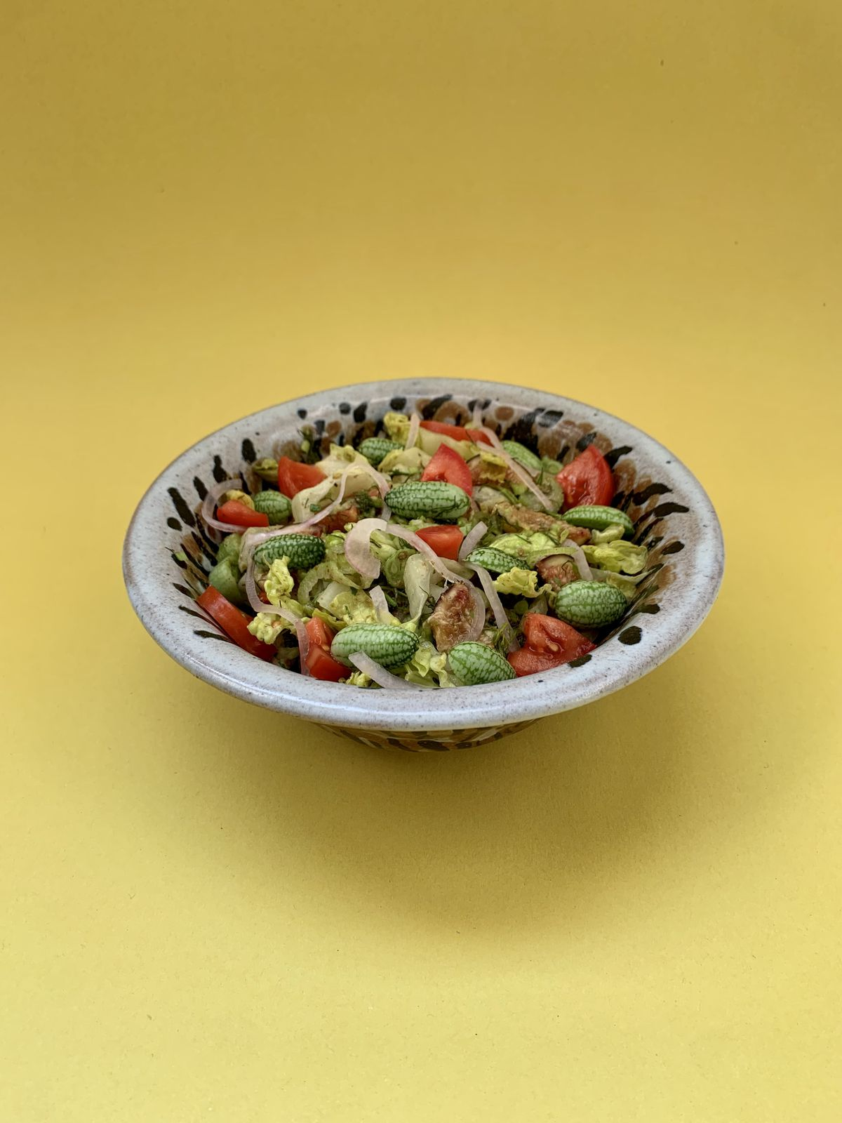 A bowl filled with a salad of romaine lettuce, tomato, fig, and watermelon gherkin on a yellow background.