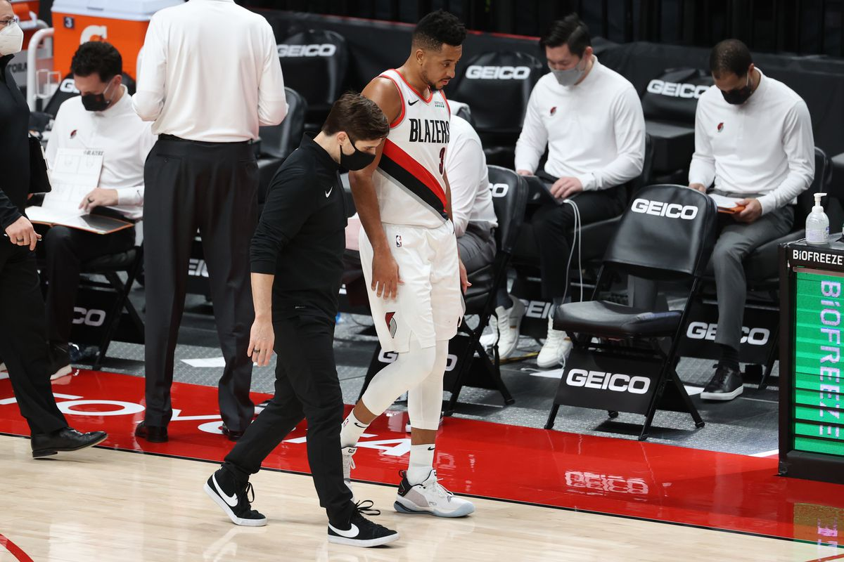 CJ McCollum of the Portland Trail Blazers has a conversation with a team attendant in the second quarter against the Atlanta Hawks at Moda Center on January 16, 2021 in Portland, Oregon.