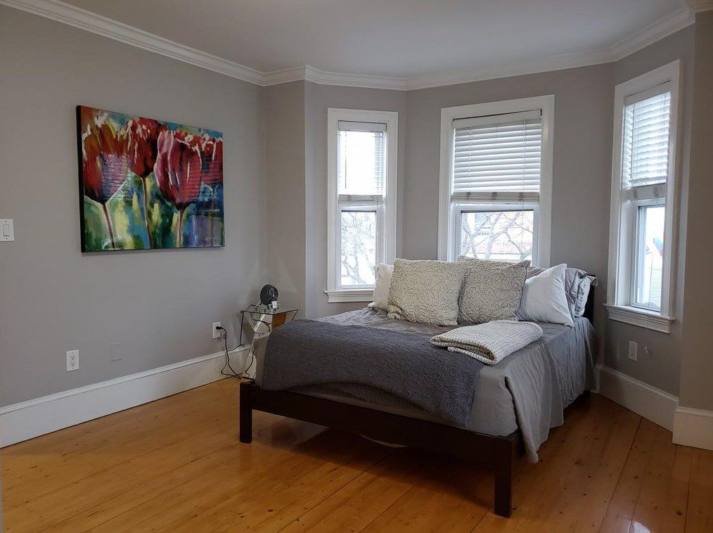 A bedroom with a bed in front of a bay window.