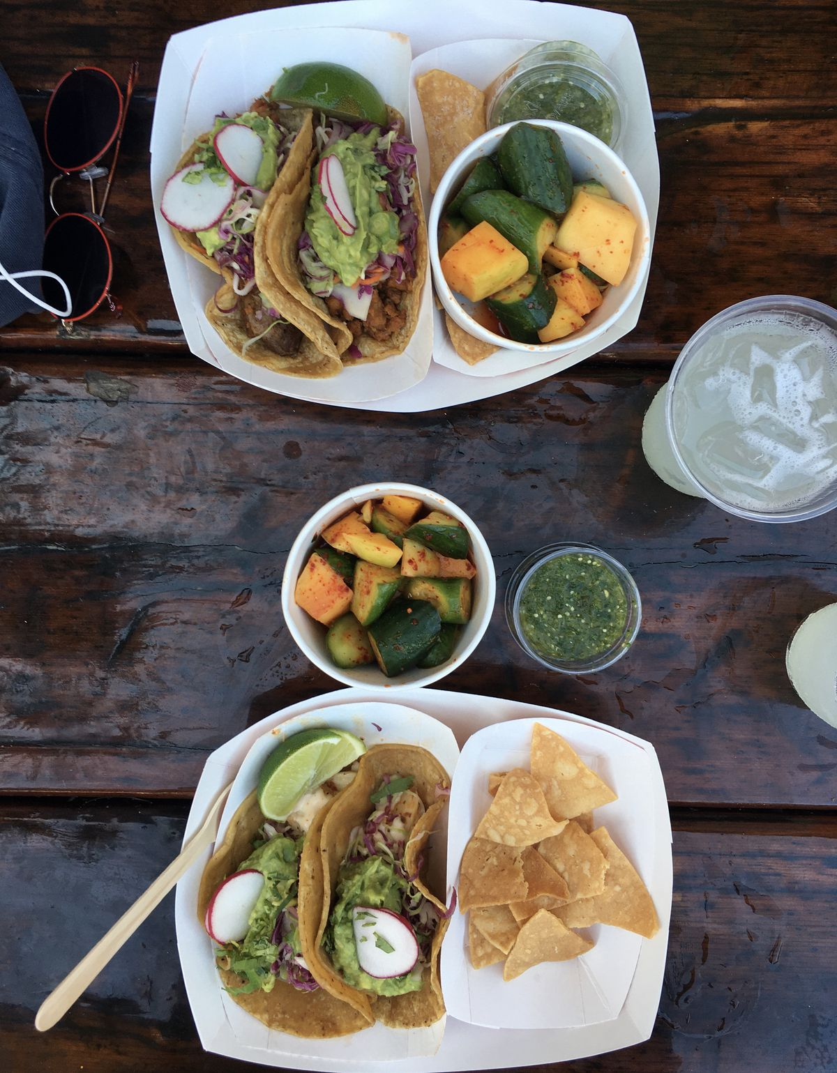 An overhead photo of to-go containers of chips, tacos, lime, radish, and summer vegetables, all of which rest on a wooden picnic table